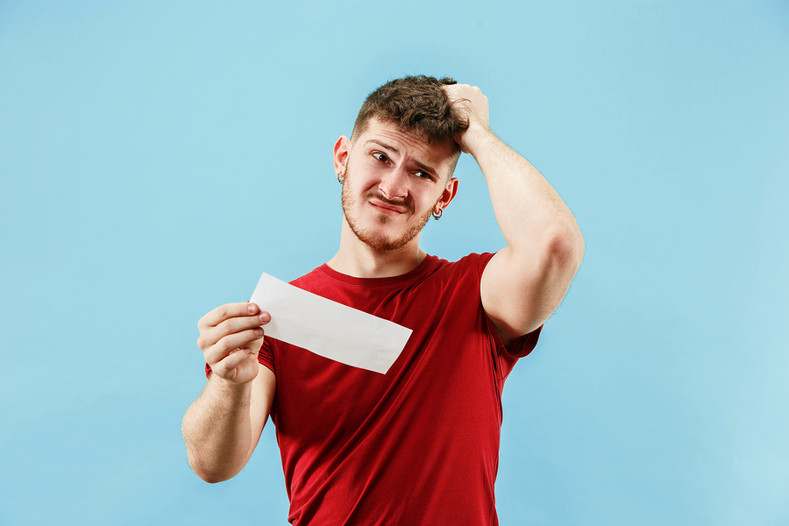 Confused man holding bet slip