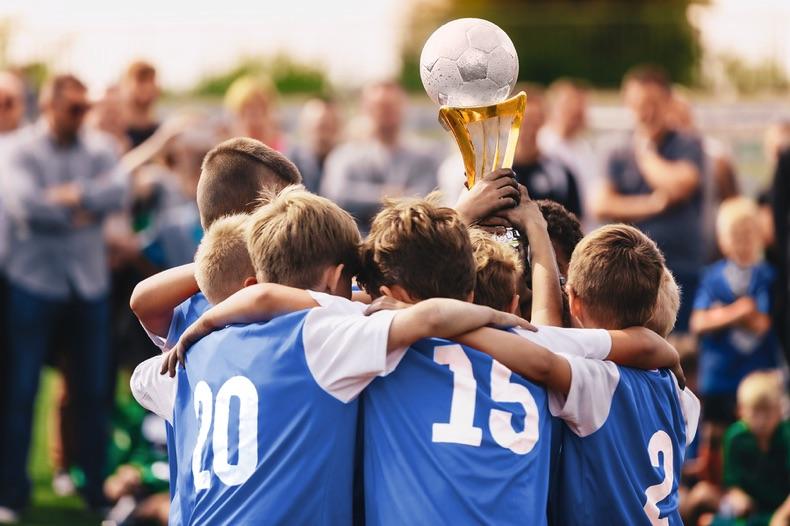 Kids winning football trophy