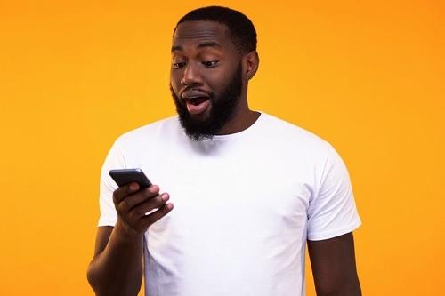 Surprised man checking phone
